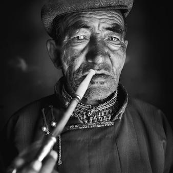 Uomo mongolo in abito tradizionale che fuma la pipa.