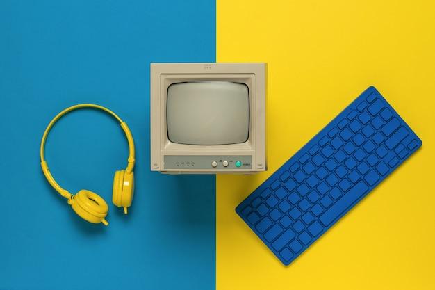 Un monitor, una tastiera blu e cuffie gialle su sfondo giallo e blu. attrezzatura d'epoca. disposizione piatta.