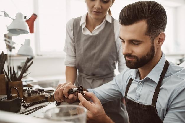 Monitoraggio dei progressi. ritratto ravvicinato di un giovane gioielliere maschio che lucida un anello mentre la maestra osserva il processo. laboratorio di creazione di gioielli. le mani del maestro