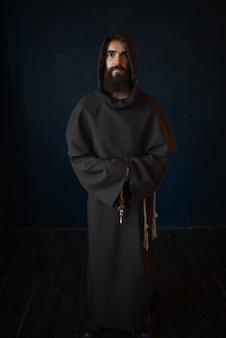 Monaco in tunica nera con cappuccio, religione. frate misterioso in mantello scuro