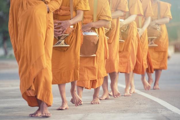 Il monaco che cammina per riceve cibo al mattino in thailandia