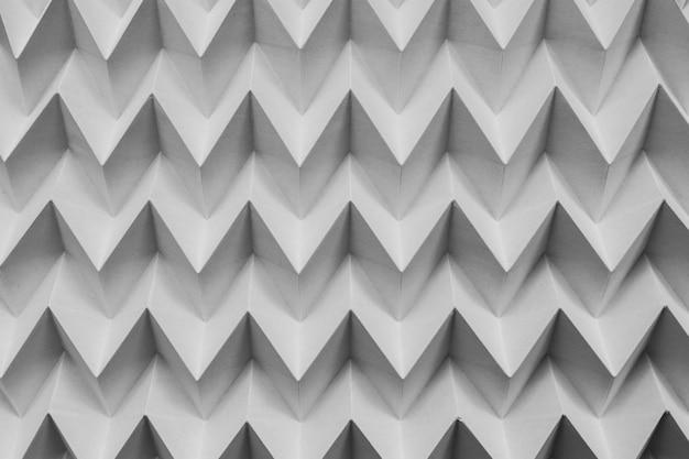 Modello futuristico del puzzle di origami piegato carta naturale astratta monocromatica