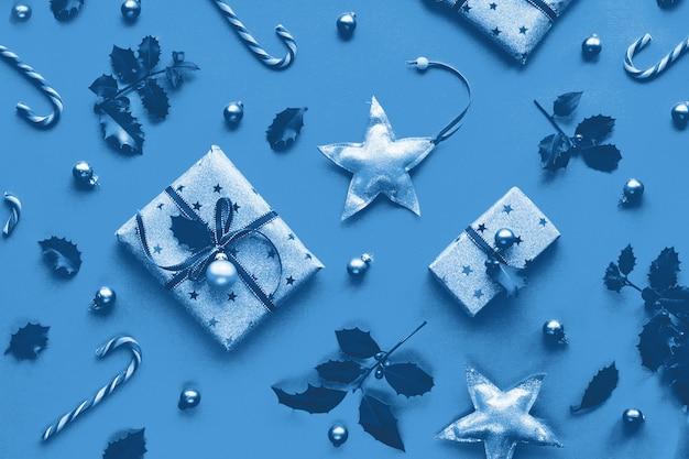 Muro di natale di colore blu monocromatico. piatto di natale geometrico alla moda disteso su una parete di carta con bastoncini di zucchero, ramoscelli di agrifoglio e abete, stelle di legno e bigiotteria di vetro. buone vacanze invernali!
