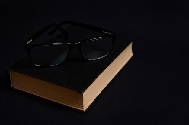 Composizione monocromatica di occhiali su un libro in copertina rigida nera, isolato su sfondo nero con spazio per il testo. concetto del giorno dell'insegnante, conoscenza, letteratura, lettura, erudizione