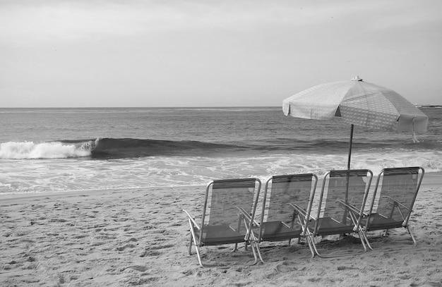 Immagine monocromatica di un gruppo di sedie a sdraio vuote con ombrellone sulla spiaggia sabbiosa