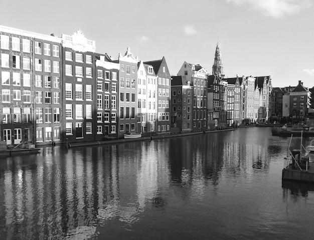 Immagine monocromatica di imponenti edifici olandesi lungo il canale di amsterdam, paesi bassi