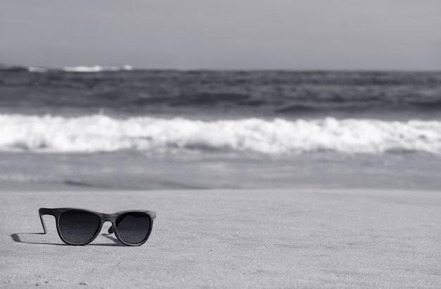 Immagine monocromatica di occhiali da sole sulla spiaggia con onde che spruzzino sfocate sullo sfondo