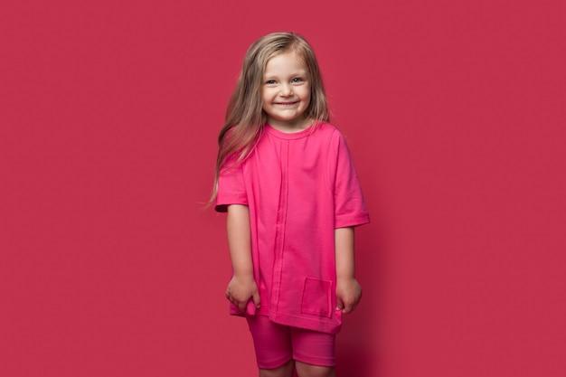 Foto monocromatica di una piccola ragazza bionda caucasica che sorride alla macchina fotografica in abbigliamento casual su una parete rossa dello studio