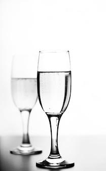 Foto monocromatica di champagne sul tavolo bianco su sfondo bianco isolare