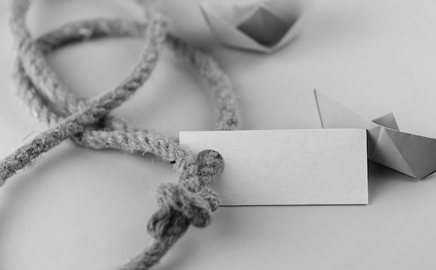 Adesivo fotografico monocromatico con corda intrecciata spessa e origami di carta nave