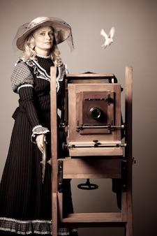 Foto retrò monocromatica di una bella donna bionda misteriosa in un abito lungo e cappello in piedi accanto a una vecchia macchina fotografica di tipo che vola oltre un uccello. concetto di arte vintage