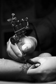 Colpo monocromatico di un tatuatore che si copre di tatuaggi su una caviglia con profondità di campo e alcune vignette