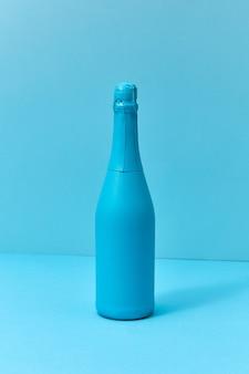 Composizione blu monotono dipinte di champagne mock up bottiglia con ombre morbide con spazio di copia. concetto minimo.