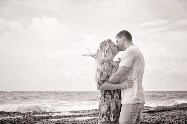 Scatto monotono di una coppia felice innamorata che si bacia sulla spiaggia in estate, stile vintage
