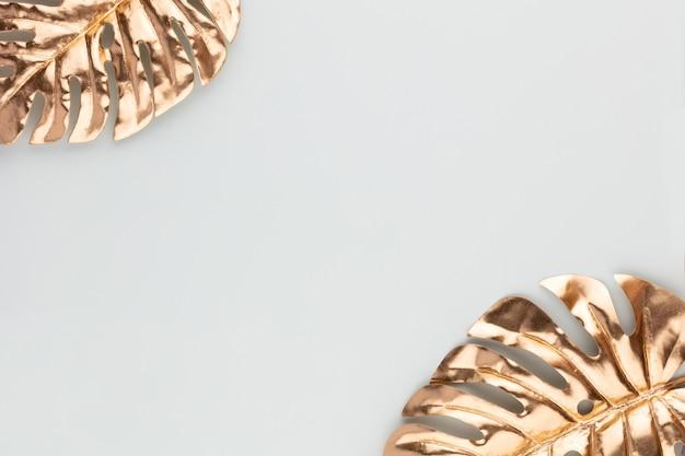 Foglia oro monstera su sfondo blu. foglia di palma, vista piatta e dall'alto.