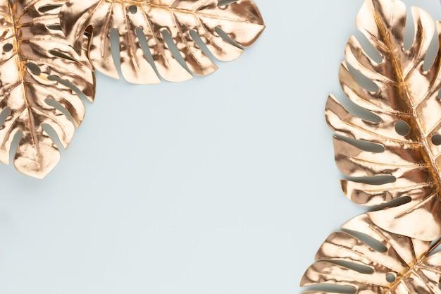 Foglia d'oro monstera su sfondo blu foglia di palma