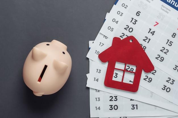 Budget mensile. pagare gli affitti per le abitazioni. salvadanaio, figurina di casa con calendario mensile su superficie grigia. vista dall'alto