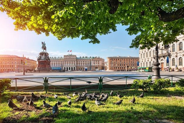 Monumento a nikolai il primo in piazza sant'isacco a san pietroburgo e piccioni sull'erba in una mattina di sole estivo