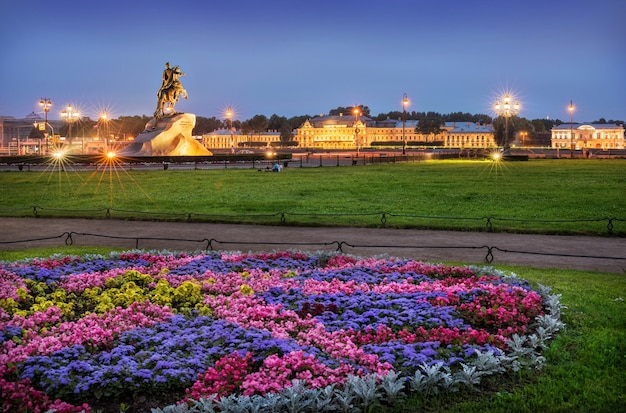 Monumento a pietro il grande, circondato da luci notturne e bellissime aiuole con fiori a san pietroburgo