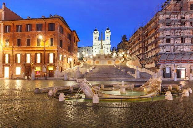 Scalinata monumentale piazza di spagna, vista da piazza di spagna, e la fontana del primo barocco chiamata fontana della barcaccia o fontana della brutta barca durante l'ora blu mattutina, roma, italia.