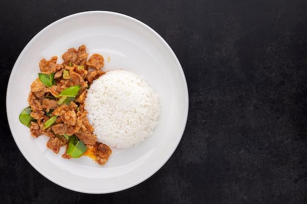 Moo pad prik gaeng, cibo tailandese, maiale fritto in padella con pasta di curry rossa, foglie di bergamotto e fagioli yardlong con riso in piatto di ceramica su sfondo texture tono scuro con copia spazio per il testo