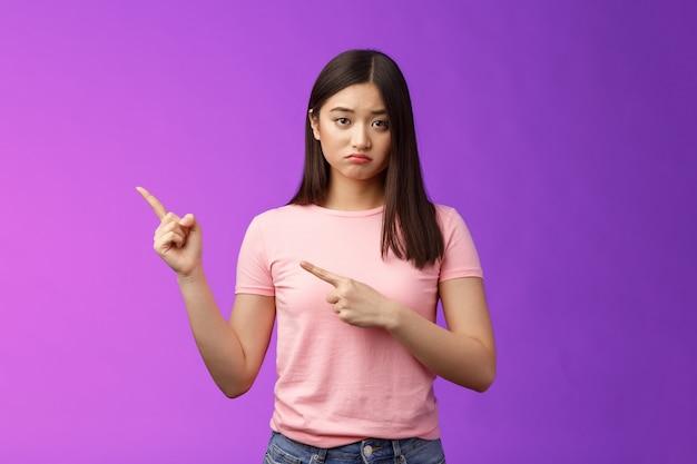 Moody sconvolta ragazza piagnucolona infelice che punta a sinistra, imbronciata sembra miserabile e angosciata, esprime rammarico e delusione, si lamenta della sfortuna, sta sullo sfondo viola scontento.