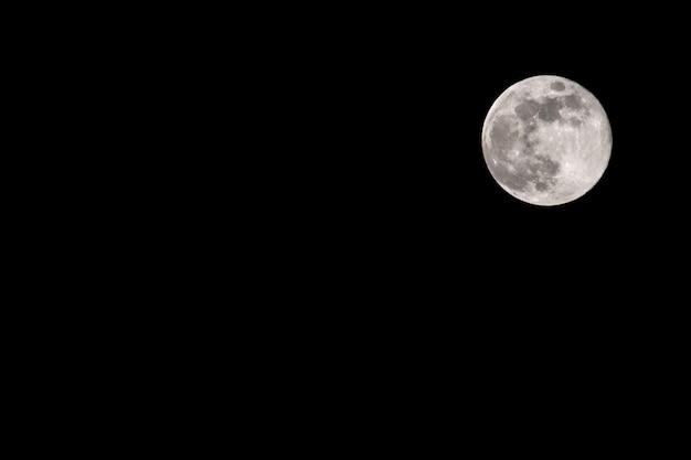 Luna contro il cielo notturno nero con copyspace