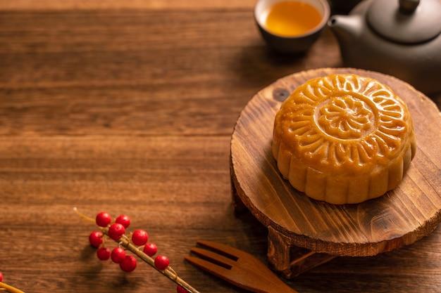 Torta di luna mooncake messa in tavola - pasticceria tradizionale cinese di forma rotonda con tazze da tè su sfondo di legno, concetto di festival di metà autunno, primo piano