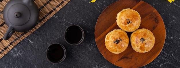 Pasta al tuorlo di torta di luna, torta di luna per le vacanze del festival di metà autunno, concetto di design vista dall'alto sul tavolo di legno scuro con spazio di copia, piatto lay