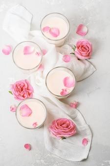 Bicchieri da bevanda al latte con rose su uno sfondo di cemento vista dall'alto.