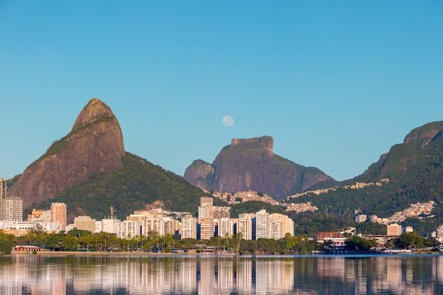 Impostazione della luna vicino alla pietra di gavea a rio de janeiro in brasile.