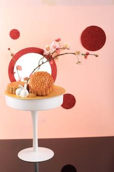 Torta di luna su sfondo rosa chiaro con concetto di fiore rosa torta di luna su festa di metà autunno m