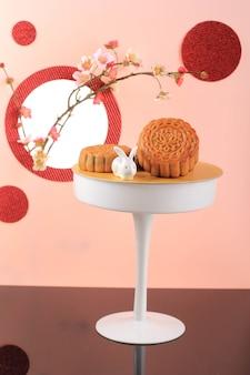 Mooncake su sfondo rosa chiaro con fiore rosa. torta della luna di concetto sul festival di metà autunno. mooncake popolare come kue bulan.