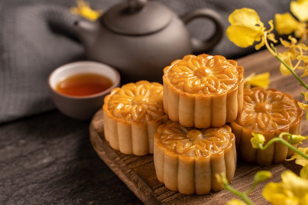 Mooncake, torta lunare per il festival di metà autunno, concetto di cibo festivo tradizionale su tavola di ardesia nera con tè e fiore giallo, primo piano, copia spazio.