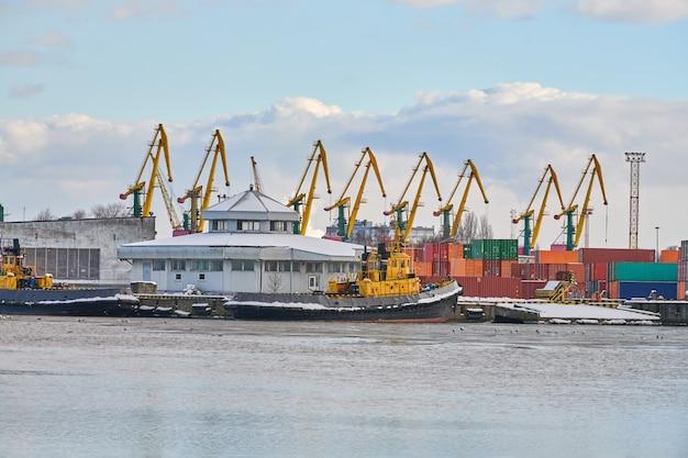 Ormeggiate navi da carico e gru portuali nel porto. porto marittimo, cantiere per container, terminal per navi portacontainer, cantiere navale. affari e commercio, logistica