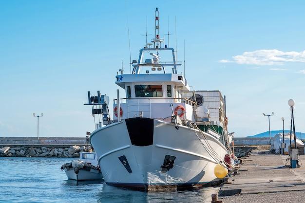 Un moderno yacht ormeggiato nel porto del mar egeo vicino a un molo, neos marmaras, grecia