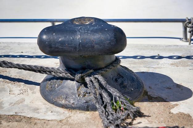 Palo di ormeggio o bitta di ormeggio con una corda legata intorno. avvicinamento
