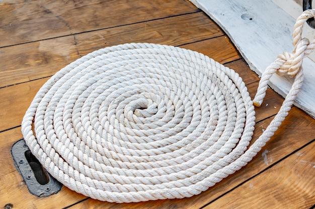 Corda di ormeggio arrotolata in anelli di rullo su una tavola di legno di una vecchia barca.