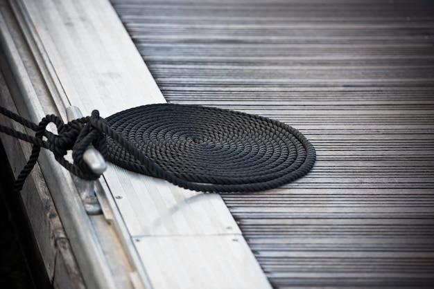 Una cima di ormeggio con un'estremità annodata legata attorno a una bitta su un molo di legno