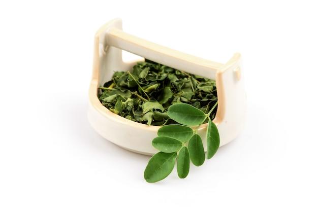 Moringa foglie verdi e polvere isolati su sfondo bianco.