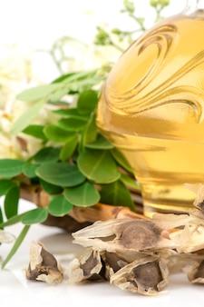 Foglie, semi ed olio verdi della moringa isolati su bianco.