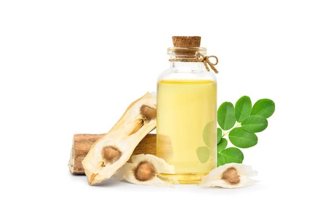 Olio di moringa in bottiglia di vetro con semi secchi e foglia verde isolato su sfondo bianco.
