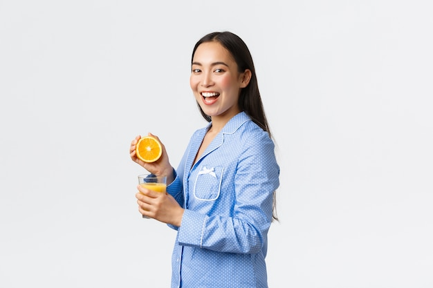 Mattina, stile di vita attivo e sano e concetto di casa. ragazza asiatica felice eccitata in pigiama che sorride alla macchina fotografica mentre spremendo l'arancia in vetro, bevendo succo d'arancia sopra priorità bassa bianca.