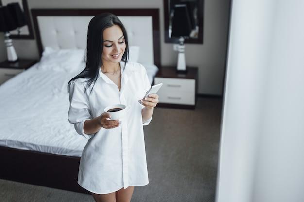 Mattina di una bella ragazza in camera d'albergo con caffè e telefono