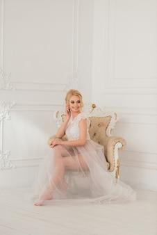 Mattina di una bella giovane sposa in un abito boudoir. studio, interni.