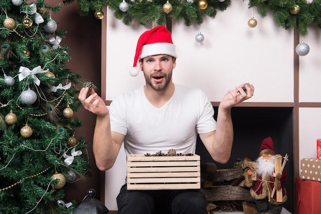 La mattina prima di natale. consegna regali di natale. felice babbo natale. acquisti natalizi online. scena del nuovo anno con regalo dell'albero. l'uomo in cappello della santa tiene il regalo di natale. buon natale. cos'è questo.
