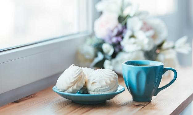 Colazione mattutina a base di caffè e marshmallow dolci sul davanzale della finestra in legno.