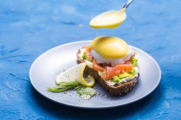 Concetto di mattina e colazione - preparazione del panino con salmone, cucchiaio sta versando la salsa su di esso.