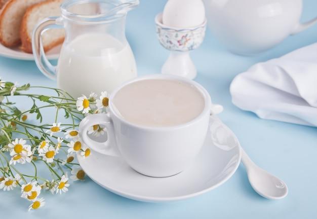Mattina. prima colazione. tazza di tè al latte, barattolo con latte, uovo su sfondo blu
