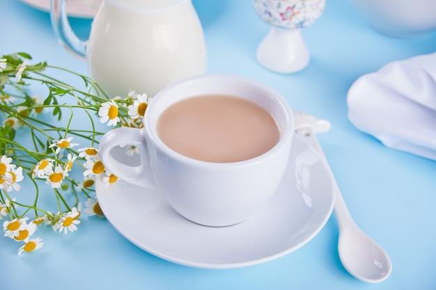 Mattina. prima colazione. tazza di tè con latte, barattolo con latte, uovo sul blu